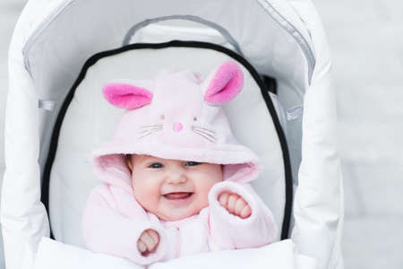 dressup: Laughing happy baby girl sitting in a white stroller in a bunny dress-up