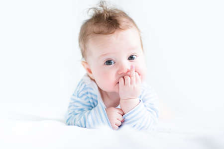 teething: Sweet baby in a blue shirt sucking on its finger