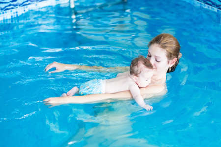 Young mother and her baby relaxing in a swimming pool  photo
