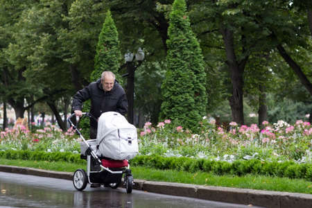 Great-grandfather walking with a stroller on a cold rainy day in a beautiful park  photo