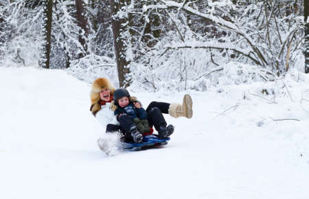 sledging people: Mother and son enjoying a sleigh ride on a beautiful winter day  Stock Photo
