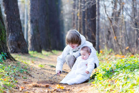 Brother and baby sister in white jackets playing in a park on a cold sunny day  photo