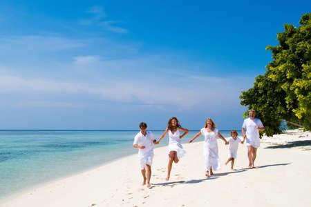 hombres corriendo: Familia de cinco celebrar un aniversario de boda que se ejecuta en una hermosa playa tropical