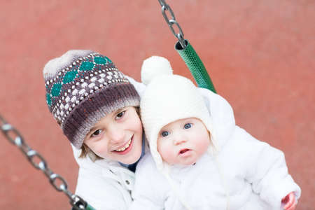 Brother and baby sister swinging in a park on a cold winter day  photo