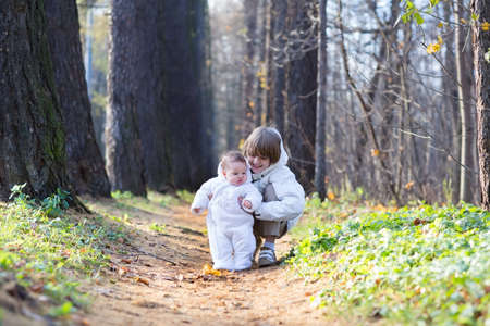 Boy playing with his baby sister in the park on a cold day  photo