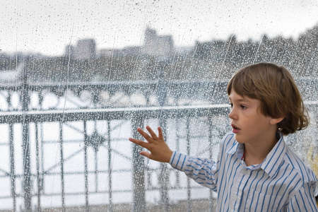 Cute boy standing next to a wet window on a rainy day  photo
