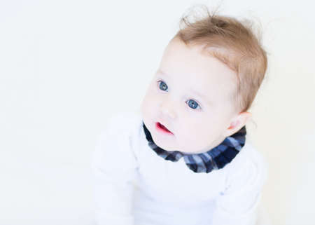 Funny smiling baby girl in a white shirt with black collar