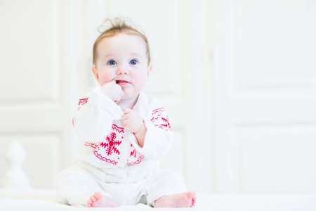 Sweet baby girl in a scandinavian knitted sweater sitting in a white nursery  photo
