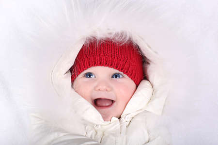 Laughing happy baby in a white snow suit and red knitted hat  photo