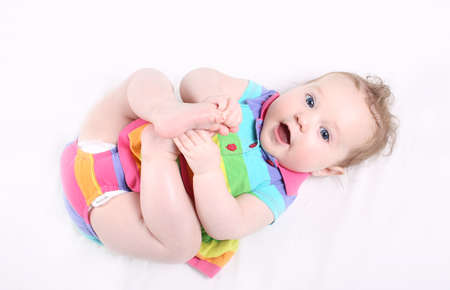Sweet baby girl in a colorful striped dress playing with her feet  photo