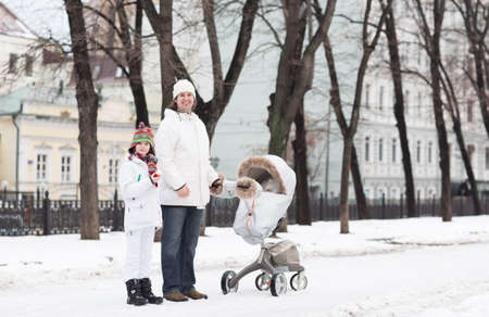 muff: Father and son walking with a baby stroller in a city park on a cold snow day