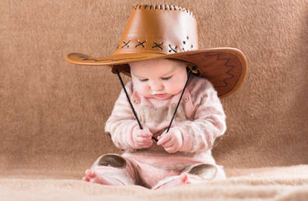Funny baby in a big cowboy hat  photo
