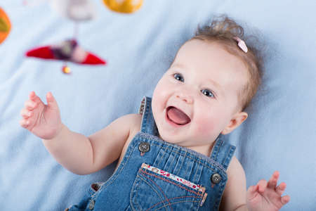 babies laughing: Sweetest baby girl playing with a colorful mobile toy  Stock Photo