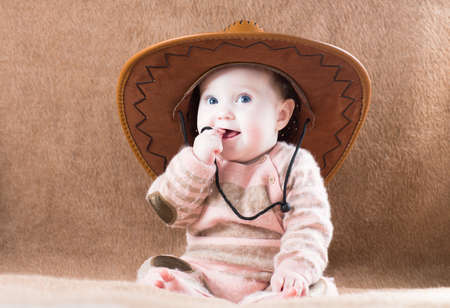 Beautiful little girl in a huge cowboy hat  photo