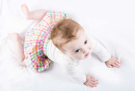 checkered skirt: Beautiful baby girl trying to crawl