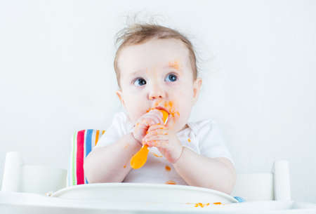흰색 높은 의자에 당근을 먹는 달콤한 지저분한 아기 스톡 콘텐츠