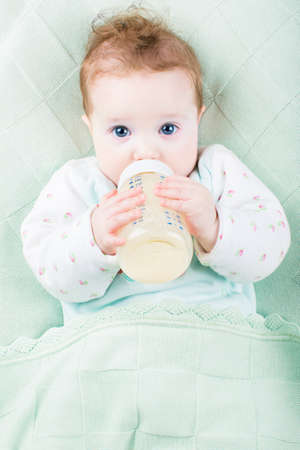baby bottle: Beautiful little baby with a milk bottle under a warm knitted blanket