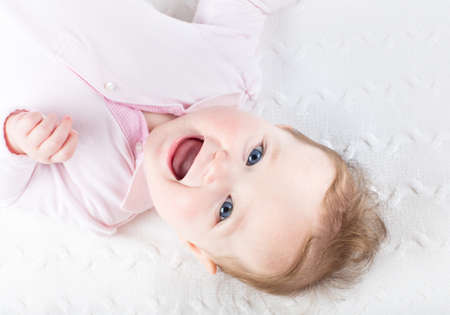 Funny laughing baby girl on a white knitted blanket Stock Photo - 29564753