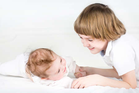 Adorable little baby girl playing with her big brother  photo