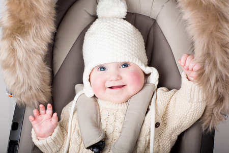 Funny little baby in a warm hat sitting in a stroller  photo