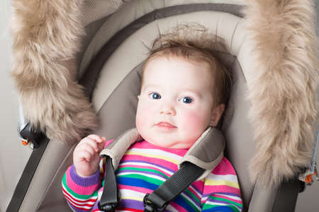 Beautiful baby girl in a pink knitted dress sitting in a stroller  photo