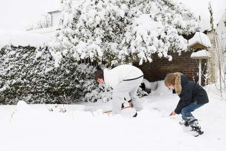 父と息子をシャベルで雪を一緒に庭園