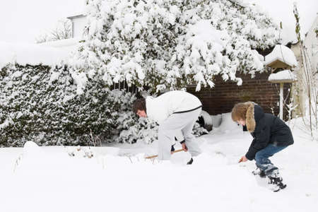 Father and son shoveling snow together in a garden  photo