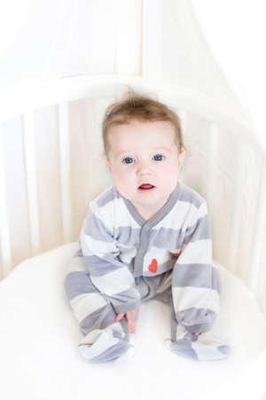 Sweet baby girl sitting in a white round crib  photo