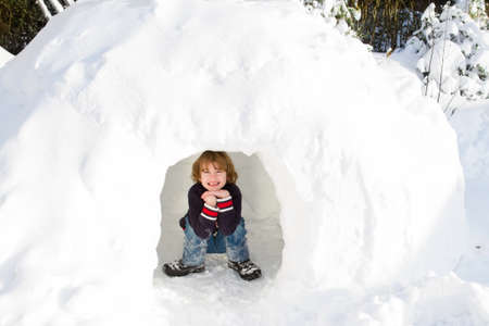 igloo: Funny boy playing in a snow igloo on a sunny winter day  Stock Photo
