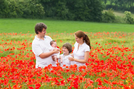 Happy young family with a son and a newborn daughter standing in a beautiful poppy flower field  photo