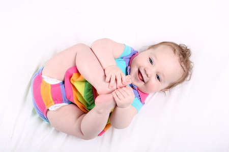 Funny chubby baby girl playing with her feet  photo