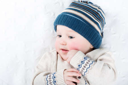 Portrait of a sweet baby in a warm knitted hat and sweater