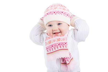 Portrait of a funny baby girl in a knitted hat, scarf and mitten, isolated on white  photo