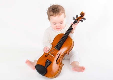 Hermosa niña jugando con un violín