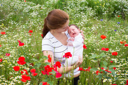 Mother and her newborn baby in a beautiful flower field  photo