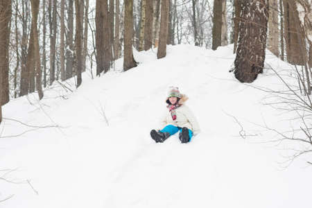 Happy laughing child riding down a snowy hill  photo