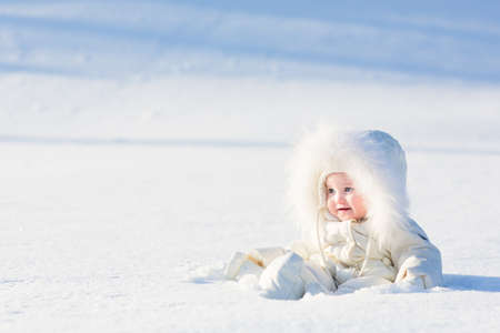 Beautiful baby in a white suit sitting in a snow field on a very sunny winter day