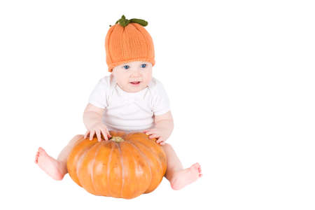 Funny baby sitting next to a pumpkin wearing a knitted pumpkin hat, isolated on white  photo