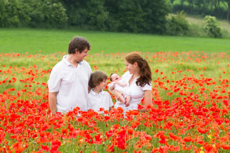 Young family with two kids - son and a newborn daughter - posing in a beautiful poppy flower field  photo