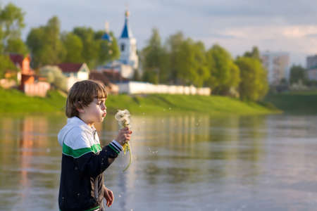 Little boy blowing dandelion with flying seeds on sunset next to a beautiful monastery on a river shore  photo