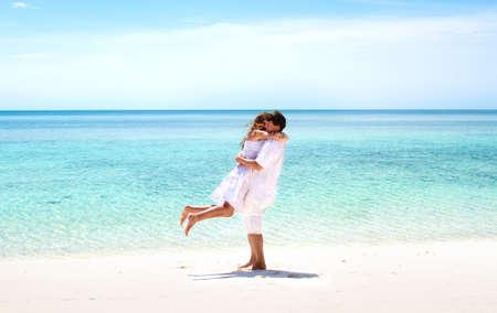 pareja bailando: Hermosa joven pareja feliz abrazando en una impresionante playa tropical