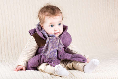 Funny baby girl in a warm purple jacket on a knitted blanket  photo