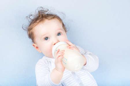 blue blanket: Cute baby with a milk bottle on a blue blanket
