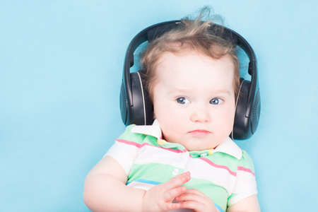 Funny little baby with big headphones  photo