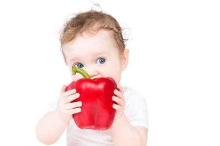 白で隔離され、大きな赤いパプリカをかむ面白い赤ちゃん