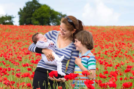 Young mother with her son and newborn baby in a beautiful red flower field  photo