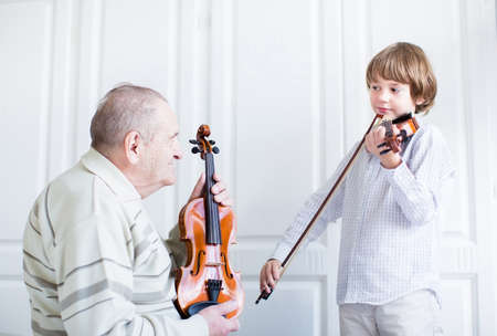grandfather grandson: Great grandfather listening to a child playing violin