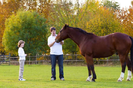 Father and son feeding a horse on a sunny autumn day