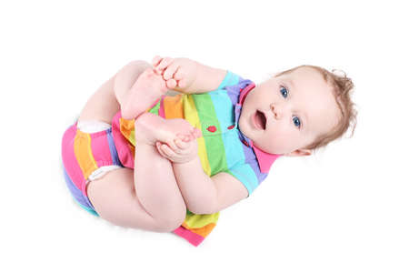 Funny baby girl playing with her feet, isolated on white  photo