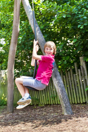 Boy playing on a swing  photo